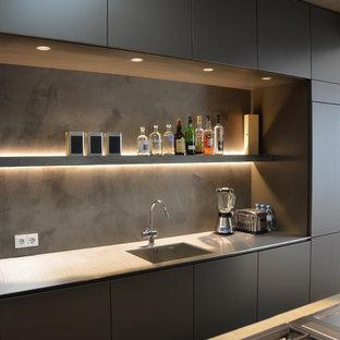 Diseño de cocina actual con fregadero bajoencimera, armarios con paneles lisos, puertas de armario grises, encimera de acero inoxidable, salpicadero verde y electrodomésticos con paneles