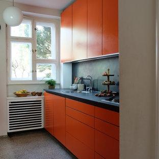 Foto de cocina contemporánea con puertas de armario naranjas, salpicadero negro, suelo de terrazo, suelo gris, fregadero bajoencimera, armarios con paneles lisos, salpicadero de azulejos de piedra, electrodomésticos de acero inoxidable y encimeras negras