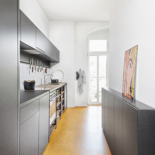 Photo of a small contemporary single-wall separate kitchen in Leipzig with a drop-in sink, flat-panel cabinets, grey cabinets, white splashback, stainless steel appliances, no island and yellow floor.