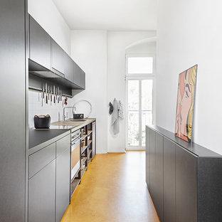 Imagen de cocina lineal, actual, pequeña, cerrada, sin isla, con fregadero encastrado, armarios con paneles lisos, puertas de armario grises, salpicadero blanco, electrodomésticos de acero inoxidable y suelo amarillo