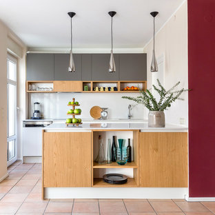 Foto på ett mellanstort funkis beige kök, med en nedsänkt diskho, släta luckor, grå skåp, bänkskiva i kvarts, beige stänkskydd, rostfria vitvaror, en köksö och rosa golv