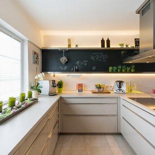 Ispirazione per una cucina design con ante lisce, ante beige e penisola