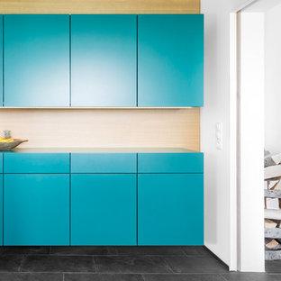 Moderne Küche mit flächenbündigen Schrankfronten, blauen Schränken, Küchenrückwand in Braun, Rückwand aus Holz und schwarzem Boden in Stuttgart