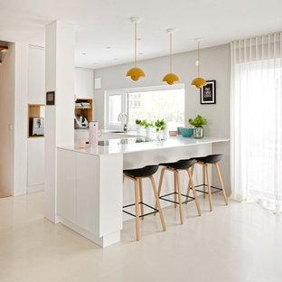 Mittelgroße Moderne Küche in U-Form mit Unterbauwaschbecken, flächenbündigen Schrankfronten, weißen Schränken, Porzellan-Bodenfliesen, Halbinsel, beigem Boden und weißer Arbeitsplatte in München