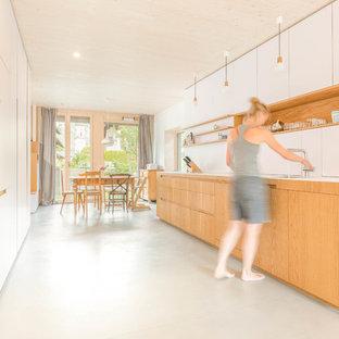 Große Moderne Wohnküche ohne Insel mit Unterbauwaschbecken, flächenbündigen Schrankfronten, Mineralwerkstoff-Arbeitsplatte, Küchenrückwand in Weiß, weißen Elektrogeräten, Betonboden, grauem Boden und weißen Schränken in München