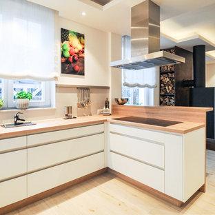 ベルリンの広いコンテンポラリースタイルのおしゃれなキッチン (ドロップインシンク、フラットパネル扉のキャビネット、白いキャビネット、木材カウンター、白いキッチンパネル、シルバーの調理設備、淡色無垢フローリング、アイランドなし、茶色い床) の写真