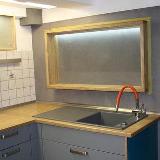 ケルンの中サイズのコンテンポラリースタイルのおしゃれなキッチン (シングルシンク、フラットパネル扉のキャビネット、淡色木目調キャビネット、木材カウンター、白いキッチンパネル、ミラータイルのキッチンパネル、黒い調理設備、クッションフロア、アイランドなし) の写真