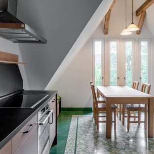 Photo of a large country galley eat-in kitchen in Other with an integrated sink, flat-panel cabinets, light wood cabinets, solid surface benchtops, black splashback, slate splashback, stainless steel appliances, porcelain floors, no island, green floor and black benchtop.