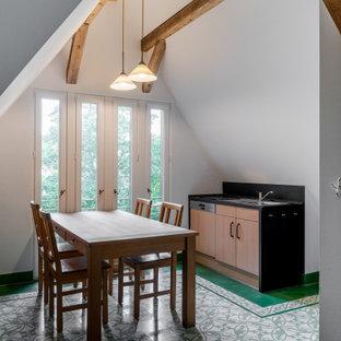 他の地域の大きいカントリー風おしゃれなキッチン (一体型シンク、フラットパネル扉のキャビネット、淡色木目調キャビネット、人工大理石カウンター、黒いキッチンパネル、スレートの床、シルバーの調理設備の、磁器タイルの床、アイランドなし、緑の床、黒いキッチンカウンター) の写真