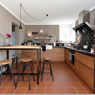 フランクフルトの中くらいのインダストリアルスタイルのおしゃれなキッチン (シングルシンク、フラットパネル扉のキャビネット、中間色木目調キャビネット、木材カウンター、黒いキッチンパネル、サブウェイタイルのキッチンパネル、シルバーの調理設備、テラコッタタイルの床、赤い床、黒いキッチンカウンター) の写真