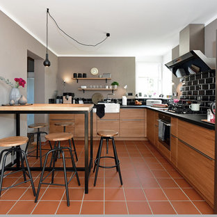 Inspiration for a mid-sized industrial l-shaped open plan kitchen in Frankfurt with a single-bowl sink, flat-panel cabinets, medium wood cabinets, wood benchtops, black splashback, subway tile splashback, stainless steel appliances, terra-cotta floors, a peninsula, red floor and black benchtop.