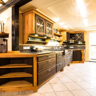 Idée de décoration pour une grande cuisine ouverte parallèle ethnique avec des portes de placard marrons, un évier de ferme, un placard à porte plane, un plan de travail en granite, une crédence grise, une crédence en dalle de pierre, un électroménager noir, un sol en carreaux de ciment, un sol beige et un plan de travail gris.