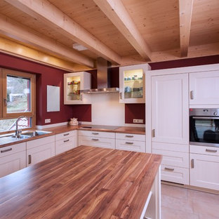 Photo of a large country l-shaped separate kitchen in Stuttgart with a drop-in sink, white cabinets, wood benchtops, red splashback, terra-cotta floors, with island, beaded inset cabinets, panelled appliances and brown benchtop.