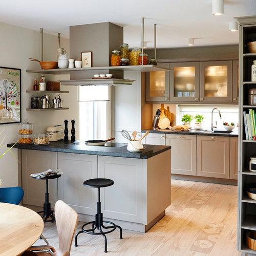 Offene mittelgroße zweizeilige moderne küche mit schwarzer arbeitsplatte schrankfronten im shaker stil