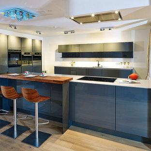 Geräumige Moderne Küche in U-Form mit Unterbauwaschbecken, flächenbündigen Schrankfronten, grauen Schränken, schwarzen Elektrogeräten, hellem Holzboden, beigem Boden und weißer Arbeitsplatte in Sonstige