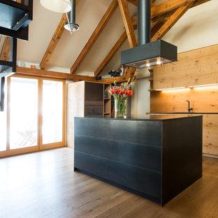 Cette image montre une cuisine ouverte parallèle asiatique de taille moyenne avec un placard à porte plane, une crédence marron, une crédence en bois, un sol en bois brun, un îlot central, un sol marron, un plan de travail noir et des portes de placard noires.