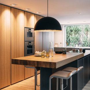 Moderne Küche in L-Form mit flächenbündigen Schrankfronten, grauen Schränken, Arbeitsplatte aus Holz, Küchengeräten aus Edelstahl, braunem Holzboden, Kücheninsel, braunem Boden und brauner Arbeitsplatte in Nürnberg