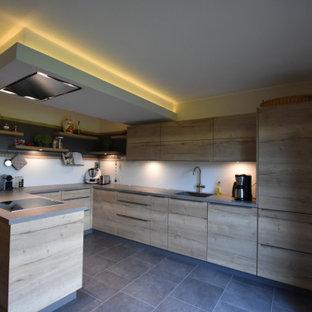 ハンブルクの中サイズのコンテンポラリースタイルのおしゃれなキッチン (シングルシンク、フラットパネル扉のキャビネット、淡色木目調キャビネット、コンクリートカウンター、白いキッチンパネル、ガラス板のキッチンパネル、パネルと同色の調理設備、クッションフロア、グレーの床) の写真