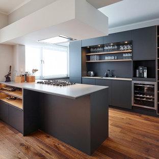 Zweizeilige, Mittelgroße Moderne Wohnküche mit Einbauwaschbecken, flächenbündigen Schrankfronten, schwarzen Schränken, Quarzit-Arbeitsplatte, Küchenrückwand in Schwarz, Küchengeräten aus Edelstahl, dunklem Holzboden, zwei Kücheninseln und braunem Boden in Düsseldorf