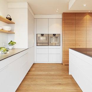 Moderne Küche in U-Form mit integriertem Waschbecken, flächenbündigen Schrankfronten, weißen Schränken, Küchenrückwand in Weiß, Küchengeräten aus Edelstahl, braunem Holzboden, Kücheninsel, braunem Boden und grauer Arbeitsplatte in Stuttgart