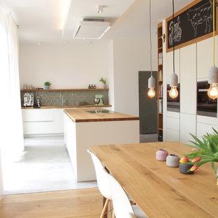 Offene, Zweizeilige, Große Skandinavische Küche mit Einbauwaschbecken, flächenbündigen Schrankfronten, weißen Schränken, Arbeitsplatte aus Holz, Küchenrückwand in Grün, Rückwand aus Metrofliesen, Küchengeräten aus Edelstahl, Betonboden, Kücheninsel und grauem Boden in Dortmund