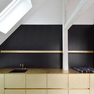 Moderne Küche mit Einbauwaschbecken, flächenbündigen Schrankfronten, Küchenrückwand in Schwarz und Betonboden in München
