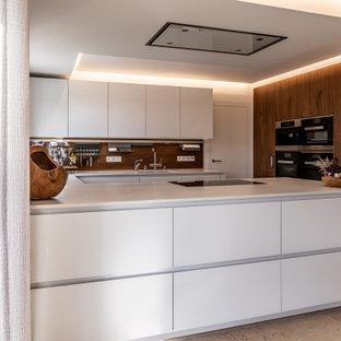 Mittelgroße Moderne Küche in U-Form mit Unterbauwaschbecken, flächenbündigen Schrankfronten, weißen Schränken, Küchenrückwand in Braun, Rückwand aus Holz, Elektrogeräten mit Frontblende, Halbinsel, braunem Boden und weißer Arbeitsplatte in Nürnberg