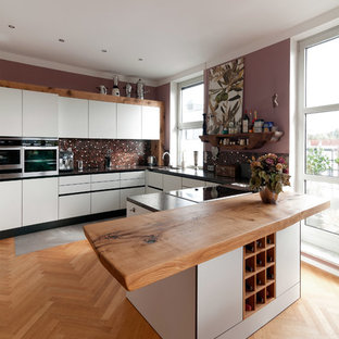 Design ideas for a large traditional u-shaped kitchen in Munich with a drop-in sink, flat-panel cabinets, white cabinets, wood benchtops, brown splashback, mosaic tile splashback, stainless steel appliances, medium hardwood floors and a peninsula.