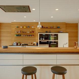 Foto di una grande cucina abitabile contemporanea con ante lisce, ante bianche, isola, paraspruzzi marrone, elettrodomestici in acciaio inossidabile e parquet chiaro