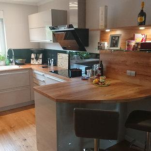 ベルリンの広いコンテンポラリースタイルのおしゃれなキッチン (ドロップインシンク、フラットパネル扉のキャビネット、グレーのキャビネット、人工大理石カウンター、黒いキッチンパネル、ガラス板のキッチンパネル、黒い調理設備、無垢フローリング、アイランドなし、茶色い床、茶色いキッチンカウンター) の写真