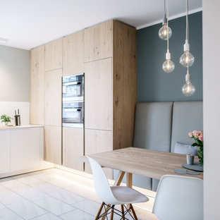Photo of a mid-sized scandinavian l-shaped eat-in kitchen in Hamburg with flat-panel cabinets, white splashback, black appliances, marble floors, no island, white floor and white benchtop.