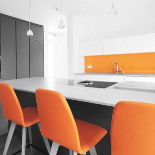 Foto på ett stort funkis kök, med en enkel diskho, släta luckor, marmorbänkskiva, orange stänkskydd, glaspanel som stänkskydd, svarta vitvaror, mellanmörkt trägolv och en köksö