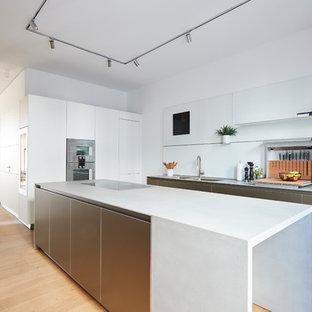 Mittelgroße Moderne Wohnküche in L-Form mit flächenbündigen Schrankfronten, Küchenrückwand in Weiß, Glasrückwand, Küchengeräten aus Edelstahl, braunem Holzboden, Kücheninsel, braunem Boden, weißer Arbeitsplatte, Doppelwaschbecken und weißen Schränken in Hamburg