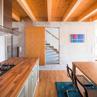 ベルリンのコンテンポラリースタイルのおしゃれなキッチン (木材カウンター、無垢フローリング、フラットパネル扉のキャビネット、グレーのキャビネット) の写真