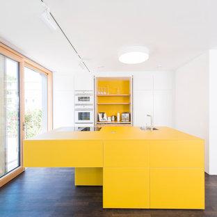 Inspiration för mellanstora moderna gult kök, med släta luckor, gula skåp, vitt stänkskydd, en köksö, rostfria vitvaror, mörkt trägolv och en enkel diskho