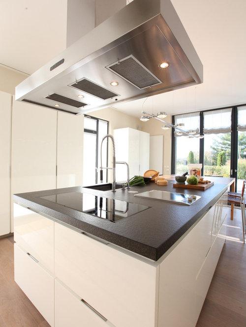 Große Moderne Wohnküche Mit Weißen Schränken, Granit Arbeitsplatte,  Flächenbündigen Schrankfronten, Braunem Holzboden