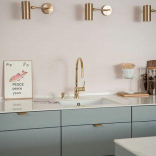 Zweizeilige, Mittelgroße Nordische Wohnküche mit Unterbauwaschbecken, flächenbündigen Schrankfronten, grauen Schränken, Küchenrückwand in Rosa, Küchengeräten aus Edelstahl, hellem Holzboden, Kücheninsel und weißer Arbeitsplatte in Sonstige