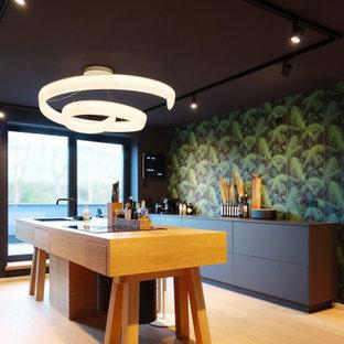 Aménagement d'une grand cuisine parallèle contemporaine avec un évier posé, un placard à porte plane, des portes de placard noires, une crédence multicolore, un îlot central, un sol marron, un plan de travail noir et un plafond en papier peint.