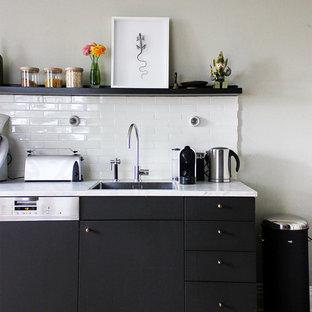 Kleine Nordische Küche mit flächenbündigen Schrankfronten, schwarzen Schränken, Küchenrückwand in Weiß, Rückwand aus Metrofliesen, Elektrogeräten mit Frontblende, dunklem Holzboden, Einbauwaschbecken, Marmor-Arbeitsplatte und braunem Boden in Hamburg