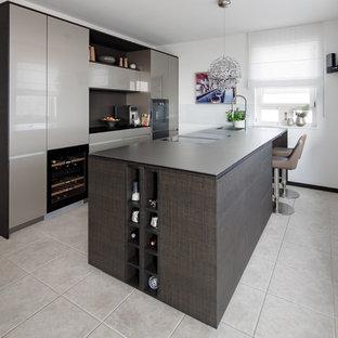 Mittelgroße, Zweizeilige Moderne Küche mit flächenbündigen Schrankfronten, grauen Schränken, schwarzen Elektrogeräten, Kücheninsel, grauem Boden und grauer Arbeitsplatte in Stuttgart