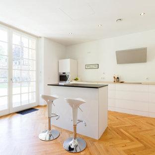 Moderne Küche in L-Form mit flächenbündigen Schrankfronten, weißen Schränken, braunem Holzboden, Kücheninsel, braunem Boden und beiger Arbeitsplatte in Essen