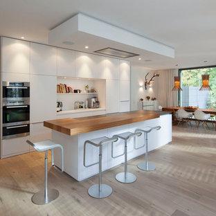ケルンの巨大なモダンスタイルのおしゃれなキッチン (フラットパネル扉のキャビネット、白いキャビネット、木材カウンター、シルバーの調理設備、無垢フローリング) の写真