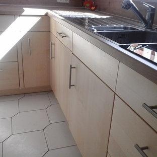 シュトゥットガルトの大きいコンテンポラリースタイルのおしゃれなキッチン (ドロップインシンク、フラットパネル扉のキャビネット、淡色木目調キャビネット、ラミネートカウンター、茶色いキッチンパネル、木材のキッチンパネル、シルバーの調理設備、セラミックタイルの床、アイランドなし、白い床、茶色いキッチンカウンター) の写真