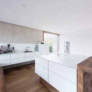 Geschlossene, Zweizeilige Industrial Küche mit flächenbündigen Schrankfronten, weißen Schränken, Küchenrückwand in Weiß, Küchengeräten aus Edelstahl, dunklem Holzboden, Kücheninsel und braunem Boden in München
