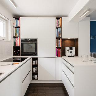 Moderne Küche in U-Form mit Einbauwaschbecken, flächenbündigen Schrankfronten, weißen Schränken, schwarzen Elektrogeräten, dunklem Holzboden, Halbinsel, braunem Boden und weißer Arbeitsplatte in Stuttgart