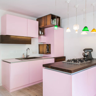Foto de cocina ecléctica con fregadero encastrado, armarios con paneles lisos, salpicadero blanco, suelo de madera clara, salpicadero de vidrio templado, península, suelo beige y encimeras rosas