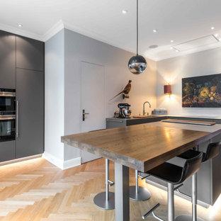 Mittelgroße Moderne Küche in L-Form mit Unterbauwaschbecken, flächenbündigen Schrankfronten, grauen Schränken, Arbeitsplatte aus Holz, Elektrogeräten mit Frontblende, hellem Holzboden, Kücheninsel, beigem Boden und brauner Arbeitsplatte in Hamburg