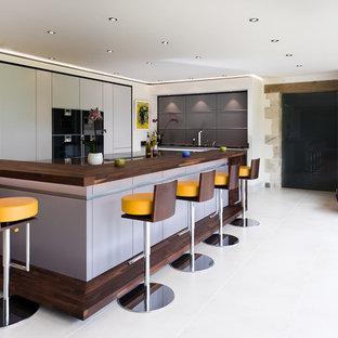 Moderne Küche in U-Form mit flächenbündigen Schrankfronten, grauen Schränken, Arbeitsplatte aus Holz, schwarzen Elektrogeräten, Kücheninsel, weißem Boden und brauner Arbeitsplatte in Stuttgart