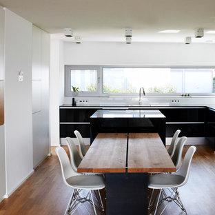 Offene, Mittelgroße Moderne Küche in L-Form mit flächenbündigen Schrankfronten, schwarzen Schränken, schwarzen Elektrogeräten, braunem Holzboden und Kücheninsel in Frankfurt am Main