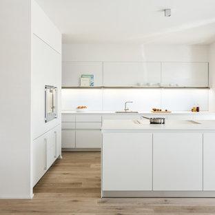 Mittelgroße Moderne Küche in L-Form mit flächenbündigen Schrankfronten, weißen Schränken, Küchenrückwand in Weiß, Glasrückwand, braunem Holzboden, Kücheninsel und braunem Boden in Stuttgart